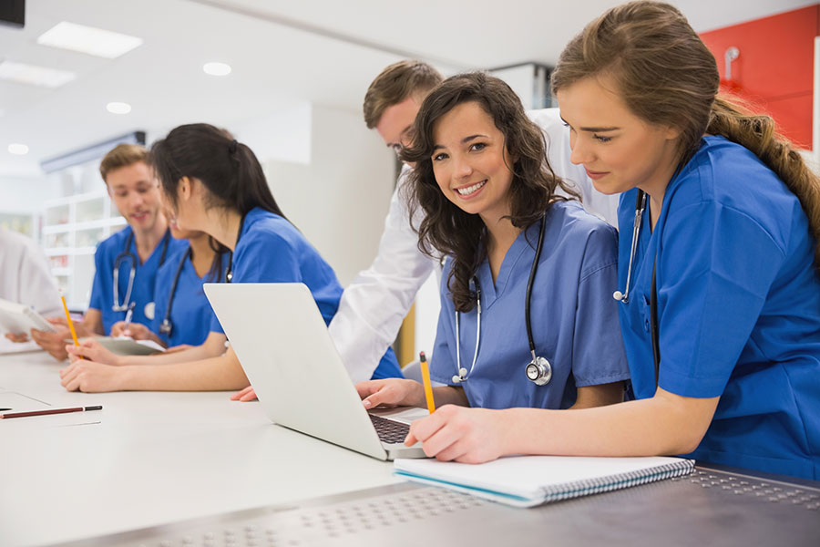 Smiling medical students looking at a computer