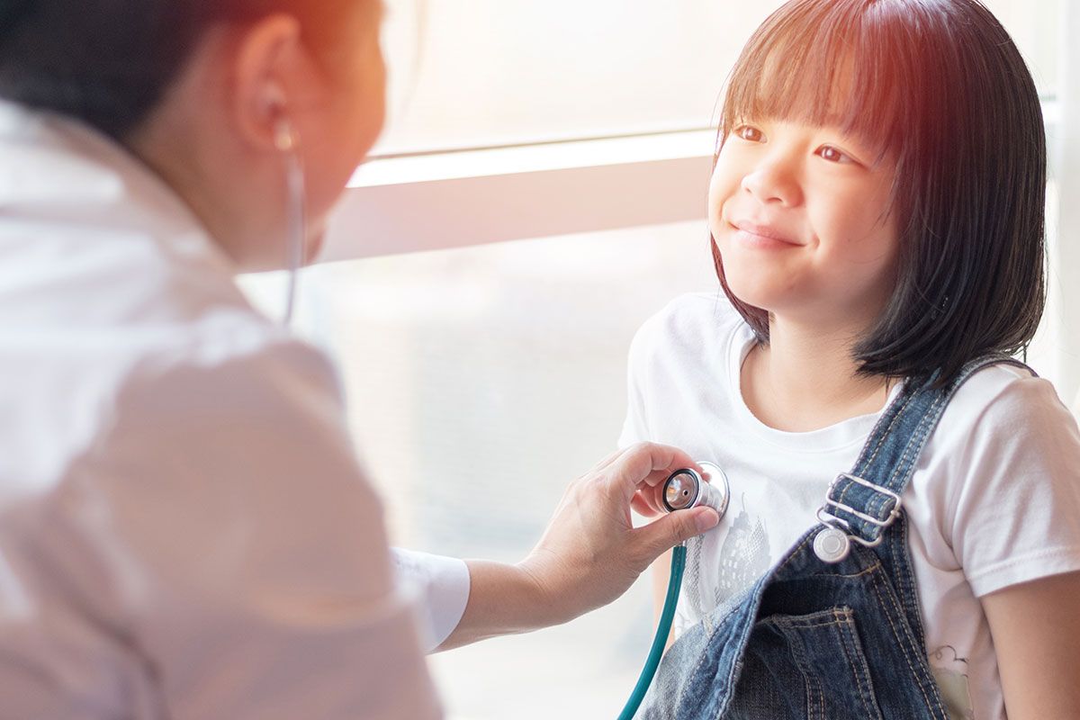A doctor checking a child's hearbeat with a stethoscope