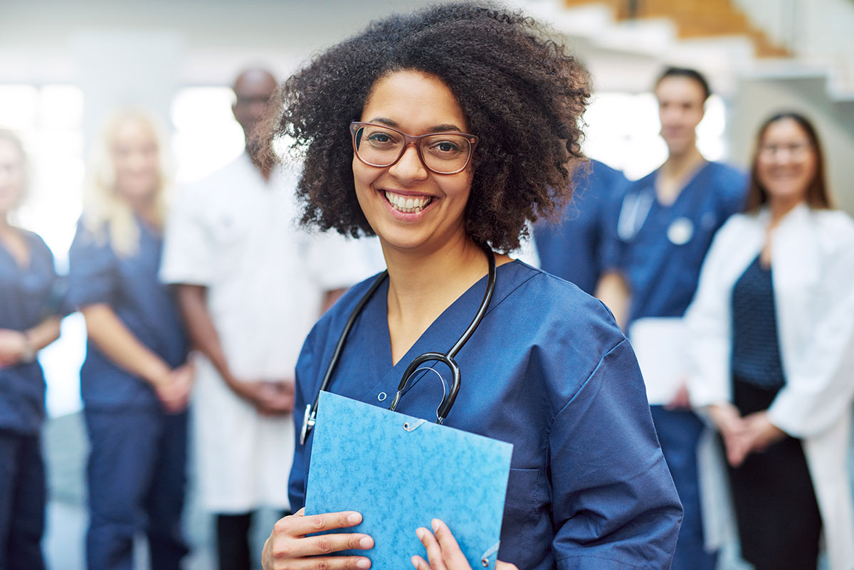 A smiling medical student holding a folder