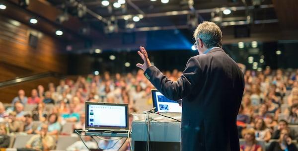 A man on stage delivering a presentation.