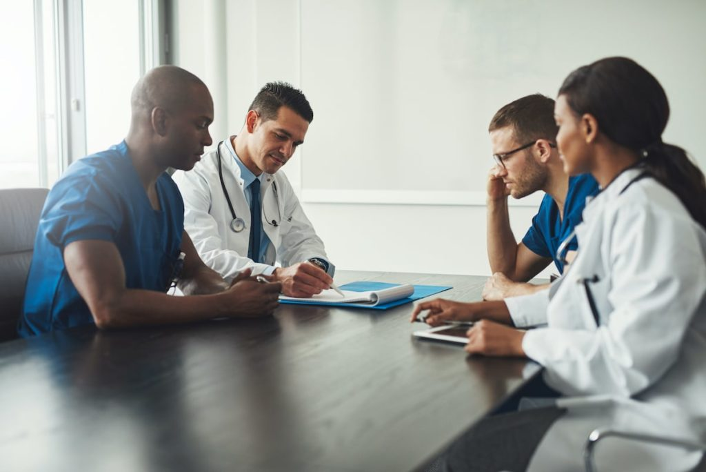 A group of medical professionals around a table having a meeting.
