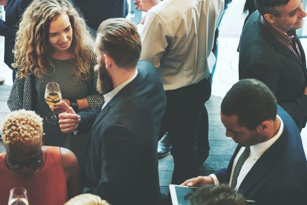 A room of people talking at a networking event.