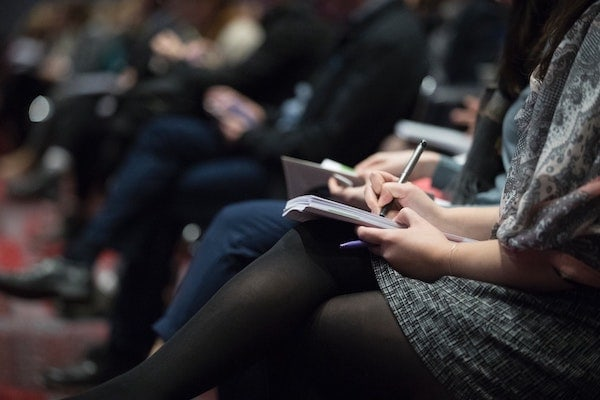 A woman attending a presentation, taking notes.