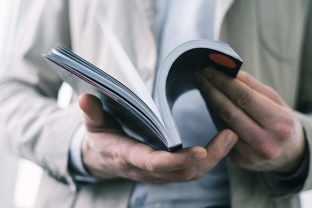 Man's hands holding open book