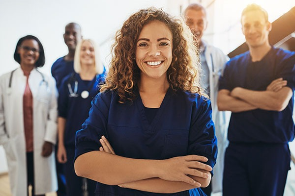 Smiling woman with doctors behind her
