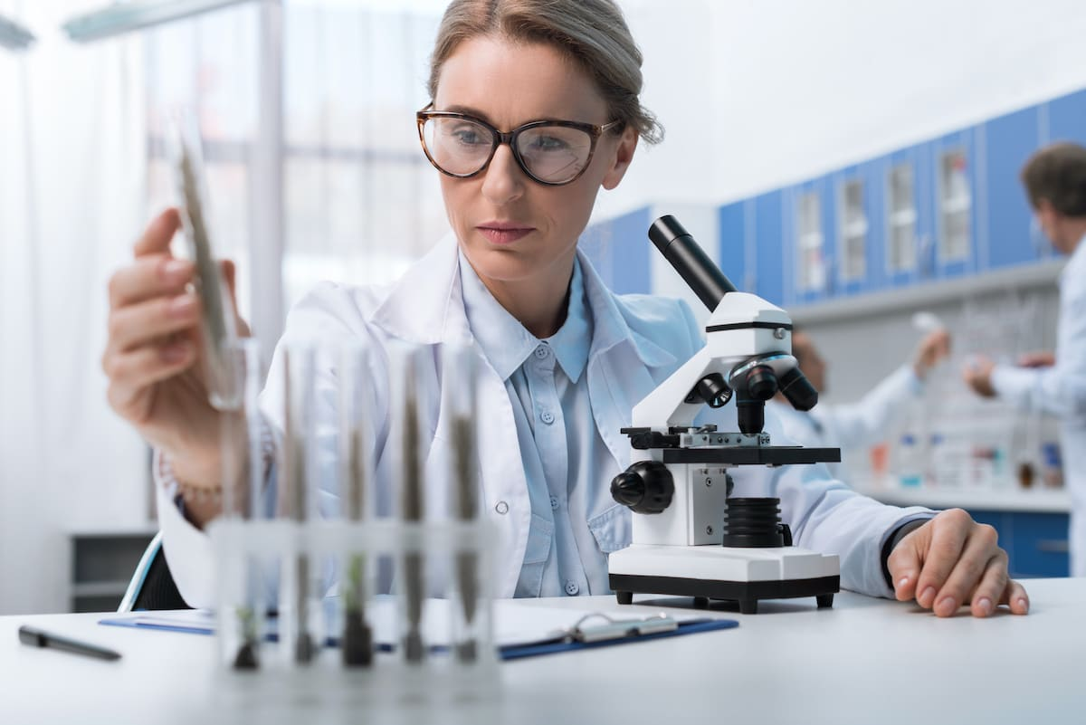 A woman in a lab conducting research with vials.